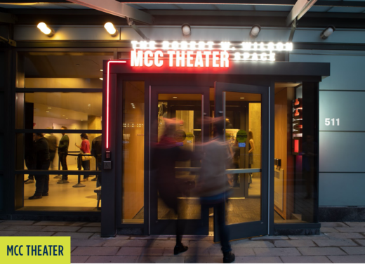 """MCC Theater: Two people walking into the theater with Neon lighting that says """"MCC Theater""""."""